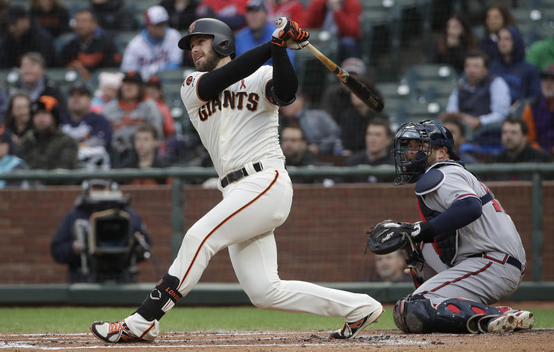 San Francisco Giants' Evan Longoria watches his RBI double in front of Atlanta Braves catcher Brian McCann during the first inning of a baseball game in San Francisco, Tuesday, May 21, 2019. (AP Photo/Jeff Chiu)