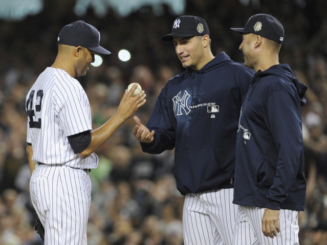CORRECTS WINNING TEAM TO RAYS - New York Yankees relief pitcher Mariano Rivera, left, hands the ball to Andy Pettitte as Derek Jeter, right, watches during the ninth inning of a baseball game against the Tampa Bay Rays on Thursday, Sept. 26, 2013, at Yankee Stadium in New York. The Rays defeated the Yankees 4-0 in Rivera's final home game with the team. (AP Photo/Bill Kostroun)