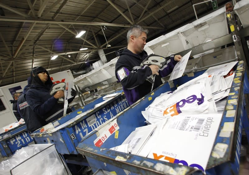 Handlers place letters and envelopes into cartons at the Marina Del Rey, California FedEx station