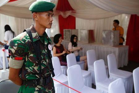 A soldier provides security at a polling booth during the Jakarta governor election in North Jakarta,