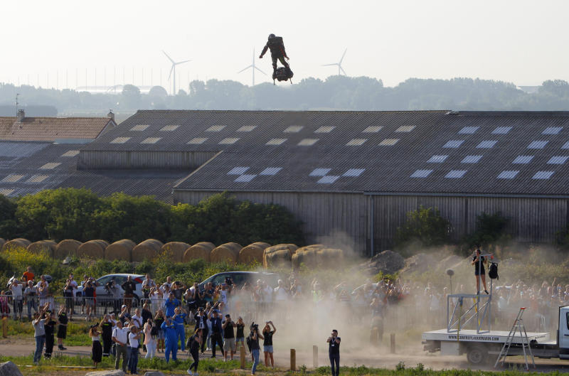 Franky Zapata, a 40-year-old inventor, takes to the air in Sangatte, Northern France, at the start of his attempt to cross the channel from France to England Thursday July 25, 2019. Zapata is anchored to his flyboard, a small flying platform he invented, taking off from Sangatte, in France's Pas de Calais region, and flying to the Dover area in southeast England. (AP Photo/Michel Spingler)