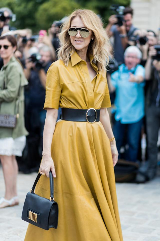 <p>Dion wears a yellow leather A-line dress with a black leather belt, Dior bag, and aviator sunglasses. (Photo: Getty) </p>