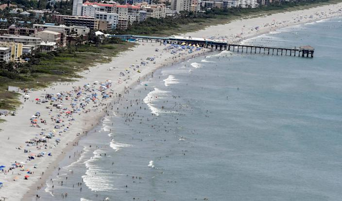 Beachgoers enjoy the sun and sand in Cocoa Beach on June 27.