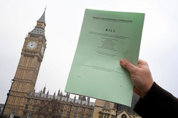 FILE PHOTO: A journalist poses with a copy of the Brexit Article 50 bill, introduced by the government to seek parliamentary approval to start the process of leaving the European Union, in London