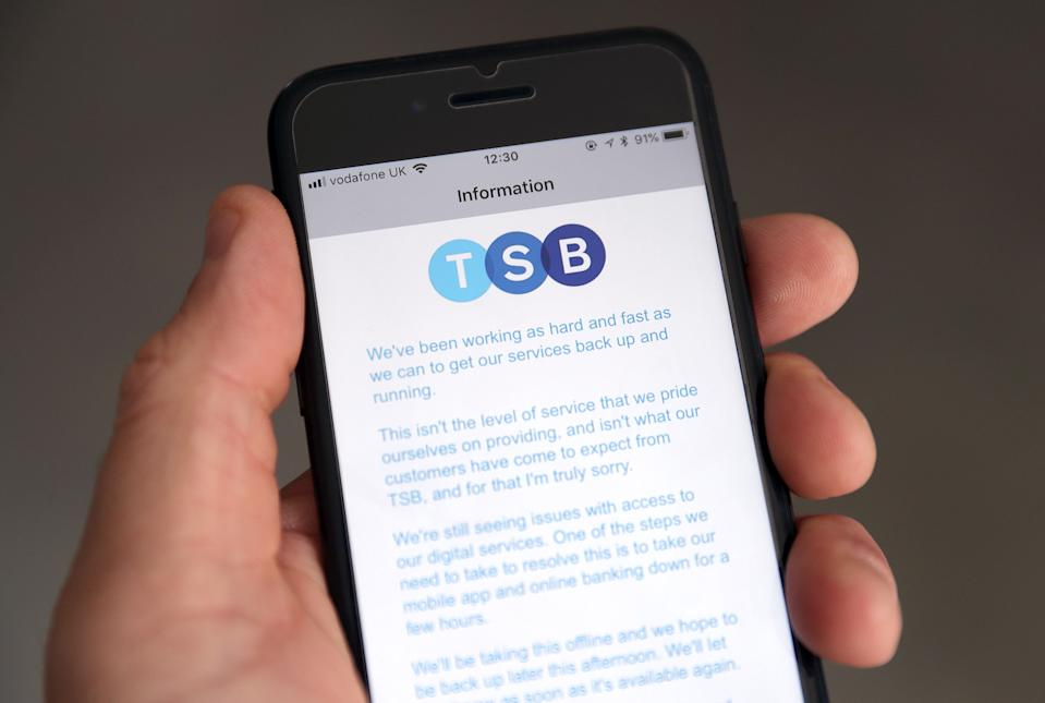 A customer using the TSB Online banking app on an iPhone reads a message from TSB CEO Paul Pester apologising for IT issues which left online customers unable to access their money and some able to see other people's accounts. (Photo by Andrew Matthews/PA Images via Getty Images)