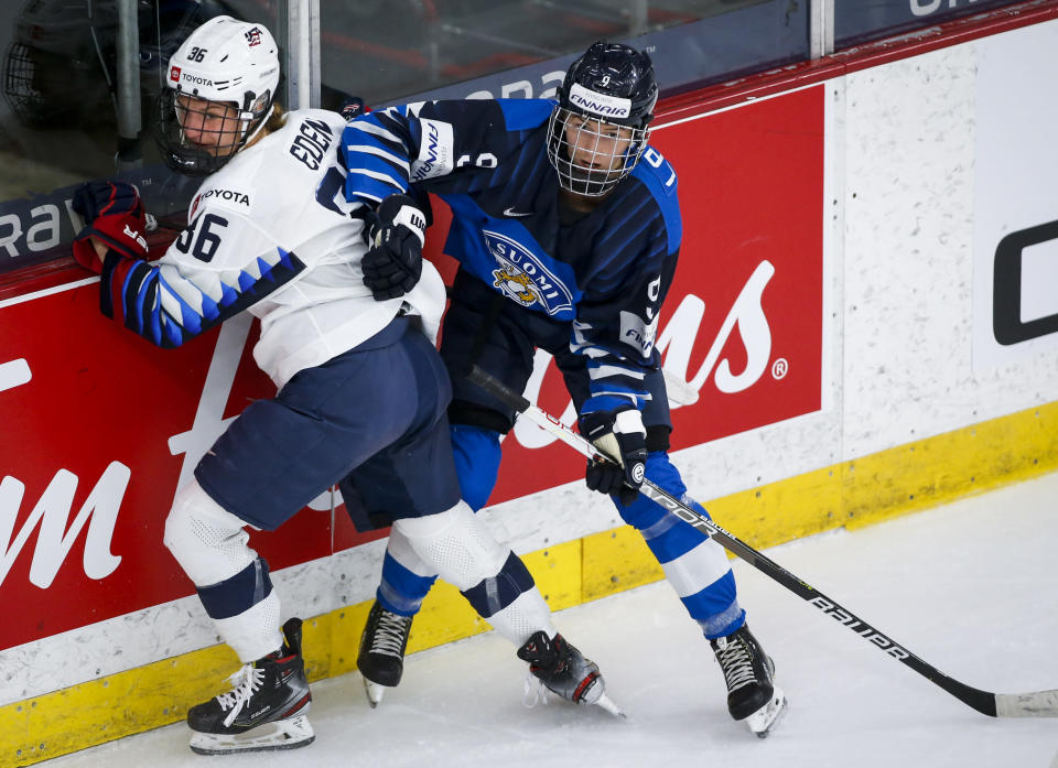 Finland's Nelli Laitinen, right, checks Lacey Eden, of the United States, during the second period of an IIHF women's hockey championships semifinal in Calgary, Alberta, Monday, Aug. 30, 2021. (Jeff McIntosh/The Canadian Press via AP)