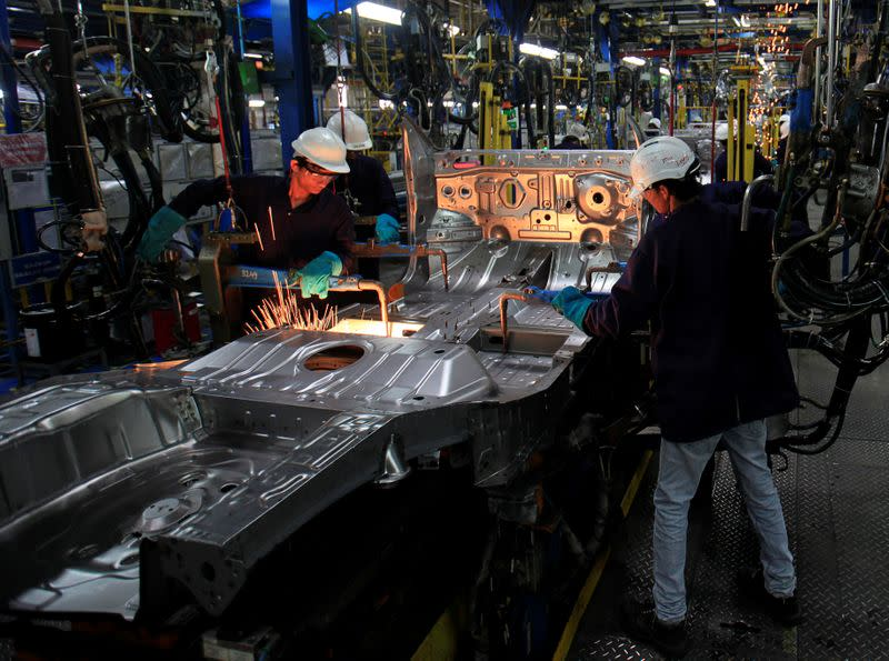 FILE PHOTO: Employees work on the assembly line at the General Motors plant in Talegaon