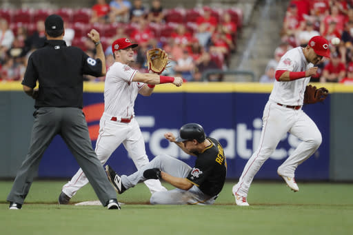 Cincinnati Reds second baseman Scooter Gennett, center left, forces out Pittsburgh Pirates' Bryan Reynolds, center right, before turning the double play at first with a force-out of Starling Marte in the fourth inning of a baseball game, Tuesday, July 30, 2019, in Cincinnati. (AP Photo/John Minchillo)
