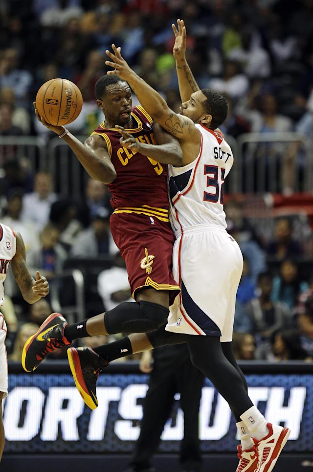 Cleveland Cavaliers' Luol Deng, of Sudan, left, passes the ball against the defense of Atlanta Hawks' Mike Scott in the third quarter of an NBA basketball game, Friday, April 4, 2014, in Atlanta. (AP Photo/David Goldman)