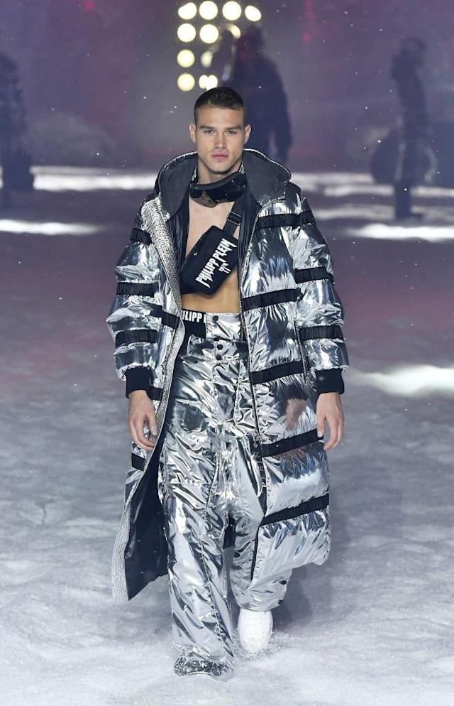 <p>Model wears a futuristic silver foil puffer coat, trousers, and fanny pack across his chest at the Philipp Plein FW18 show. (Photo: Getty) </p>