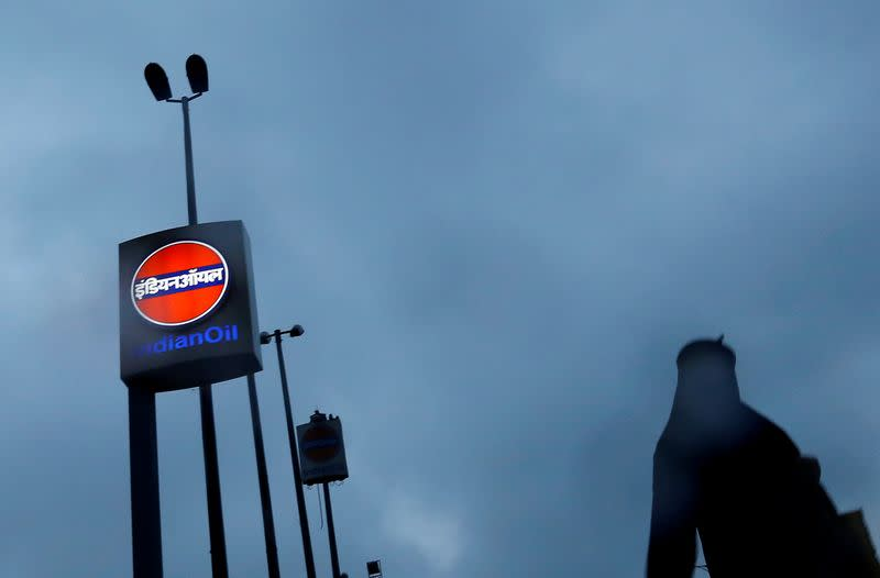 FILE PHOTO: A woman walks past a logo of Indian Oil outside a fuel station in New Delhi