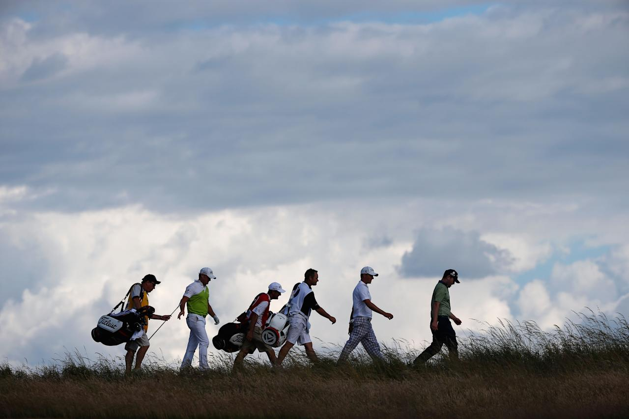 GULLANE, SCOTLAND - JULY 18: Webb Simpson of the United States, Jamie Donaldson of Wales and Branden Grace of South Africa walk off the 12th tee with their caddies during the first round of the 142nd Open Championship at Muirfield on July 18, 2013 in Gullane, Scotland. (Photo by Rob Carr/Getty Images)