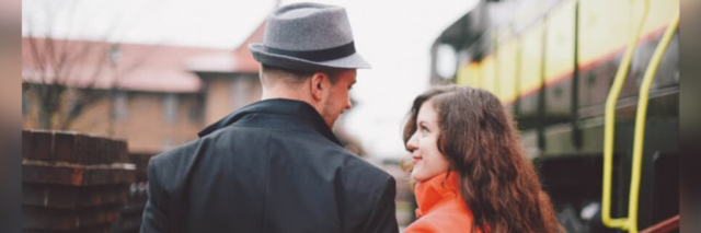 A man wearing a hat and a woman in a bright red/orange coat looking lovingly at each other