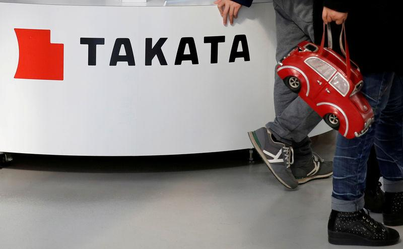 Visitors walk past a logo of Takata Corp on its display at a showroom for vehicles in Tokyo, Japan