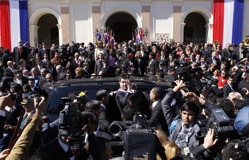 Paraguay's new President Horacio Cartes waves from a car, center, as he leaves the Cathedral after he took office in Asuncion, Paraguay, Thursday, Aug. 15, 2013. Cartes, 57, is a multimillionaire who built a family fortune by dominating industries from banking to tobacco to soft drinks to soccer. (AP Photo/Cesar Olmedo)