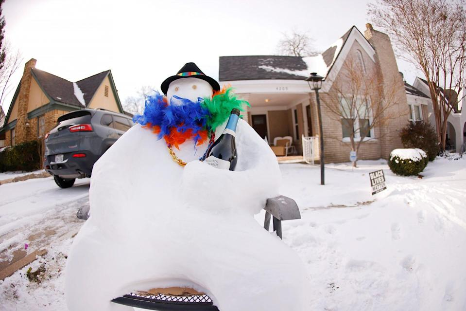 <p>A snowman holds a bottle of wine in honor of Mardi Gras on Feb. 16 in Fort Worth, Texas.</p>