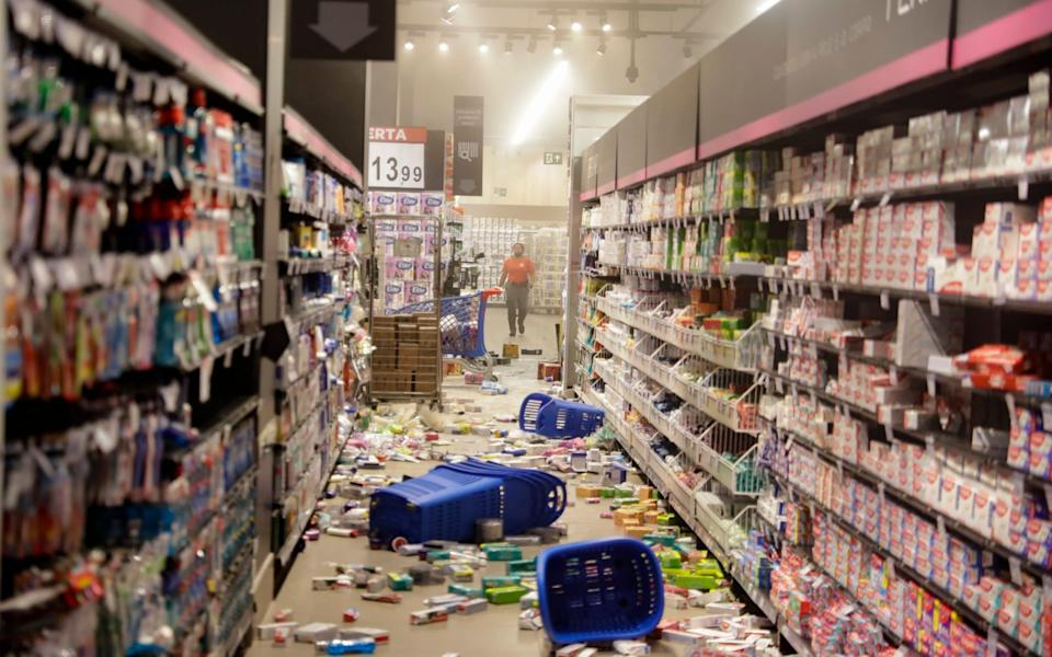 Groceries litter the floor - Andre Penner/AP