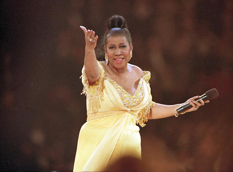 <p>Aretha Franklin wears a yellow empire dress with beaded details along the sleeve and bust while performing at the inaugural gala for U.S. President Bill Clinton in Washington D.C. (AP Photo/Amy Sancetta) </p>