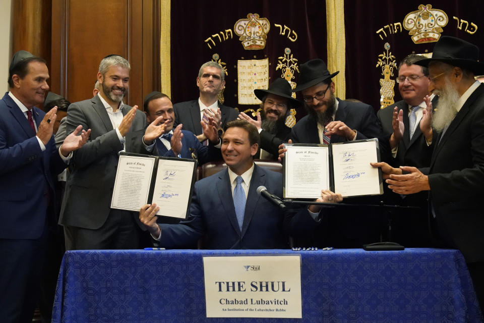 Surrounded by state legislators and Jewish leaders, Florida Gov. Ron DeSantis, center, holds up two bills that he signed, Monday, June 14, 2021, at the Shul of Bal Harbour, a Jewish community center in Surfside, Fla. DeSantis visited the South Florida temple to denounce anti-Semitism and stand with Israel, while signing a bill into law that would require public schools in his state to set aside moments of silence for children to meditate or pray. (AP Photo/Wilfredo Lee)