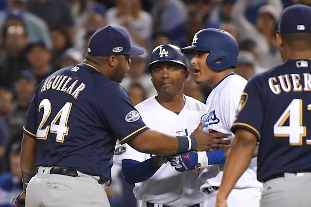 Manny Machado and Jesús Aguilar exchange words during the 10th inning after the Dodgers shortstop whacked Aguilar's leg with his own as he crossed the bag. (Getty Images)