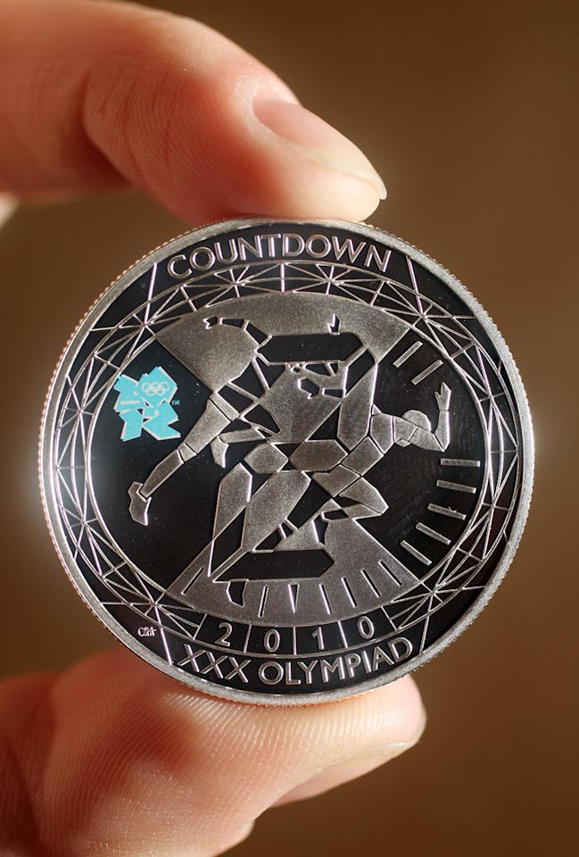 A woman holds a London 2012 countdown commemorative coin at the launch of the London Olympic Games official merchandise on July 30, 2010 in London, England. The merchandise is being launched with two years to go before the Games begin and features a range of goods including: clothing, towels, bedding, ceramics, stamps, coins, badges, mascot toys and soft furnishings.  (Photo by Oli Scarff/Getty Images)