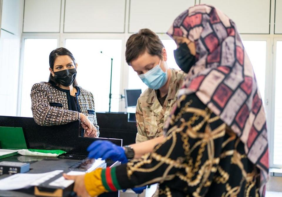 Home Secretary Priti Patel, left, watches as Afghan refugees are processed at Heathrow Airport (Dominic Lipinski/PA) (PA Wire)