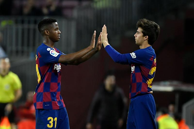 Barcelona's Spanish midfielder Riqui Puig (R) replaces Barcelona's Guinea-Bissau forward Ansu Fati (L) during the Spanish league football match between FC Barcelona and Levante UD at the Camp Nou stadium in Barcelona, on February 2, 2020. (Photo by LLUIS GENE / AFP) (Photo by LLUIS GENE/AFP via Getty Images)