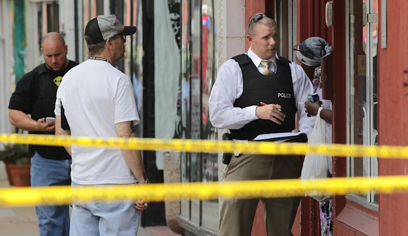 St. Louis police work the scene where four people were found dead in a business along Cherokee Street south of downtown in St. Louis, on Thursday, June 13, 2013. The St. Louis Police Department posted on its official Twitter account that two women and two men are dead. (AP Photo/St. Louis Post-Dispatch, Robert Cohen) EDWARDSVILLE INTELLIGENCER OUT; THE ALTON TELEGRAPH OUT