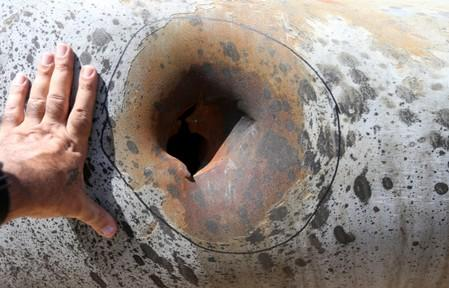 A hole in a damaged pipeline is seen at Saudi Aramco oil facility in Khurais