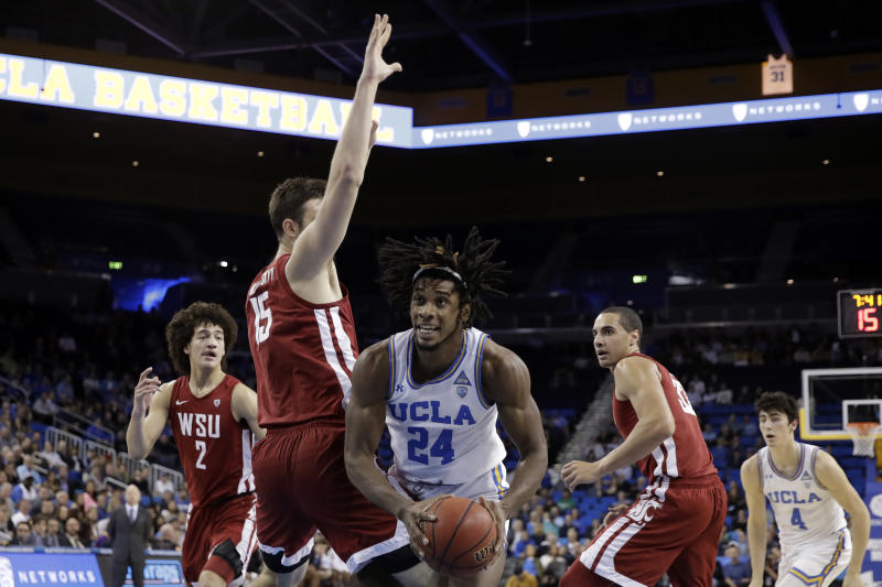 UCLA forward Jalen Hill (24) is defended by Washington State center Volodymyr Markovetskyy (15) during the first half of an NCAA college basketball game Thursday, Feb. 13, 2020, in Los Angeles. (AP Photo/Marcio Jose Sanchez)