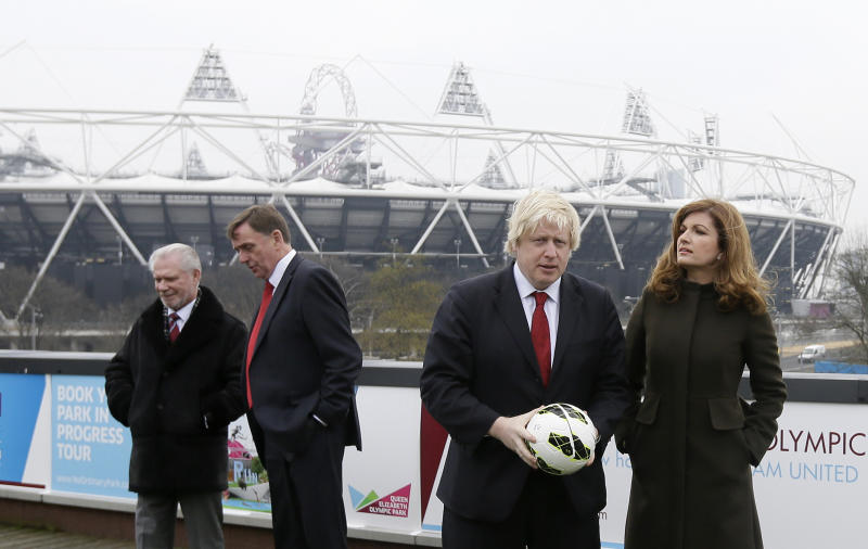 Mayor of London Boris Johnson, second right, with Karen Brady, vice chairman of English Premier League soccer team West Ham United, pose for the media on a balcony overlooking the London 2012 Olympic summer games stadium London, Friday, March, 22, 2013. The stadium built for the summer games has had its future secured in a deal where a local English Premier League team West Ham United will have a 99 year lease to use the stadium starting in 2016, it was announced at a press conference in (AP Photo/Alastair Grant)