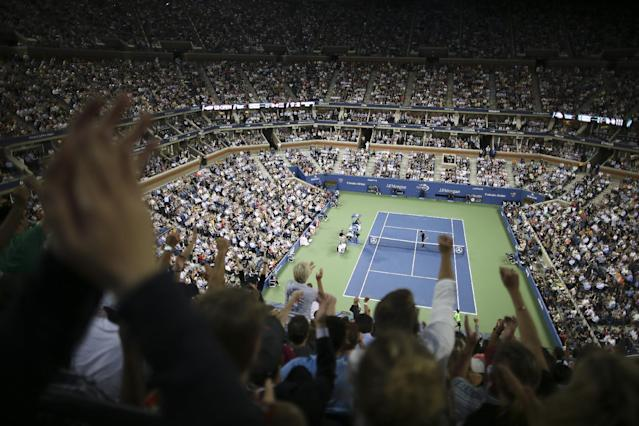 Spectators cheer during a quarterfinal between Roger Federer, of Switzerland, and Gael Monfils, of France, at the U.S. Open tennis tournament, Thursday, Sept. 4, 2014, in New York. (AP Photo/John Minchillo)