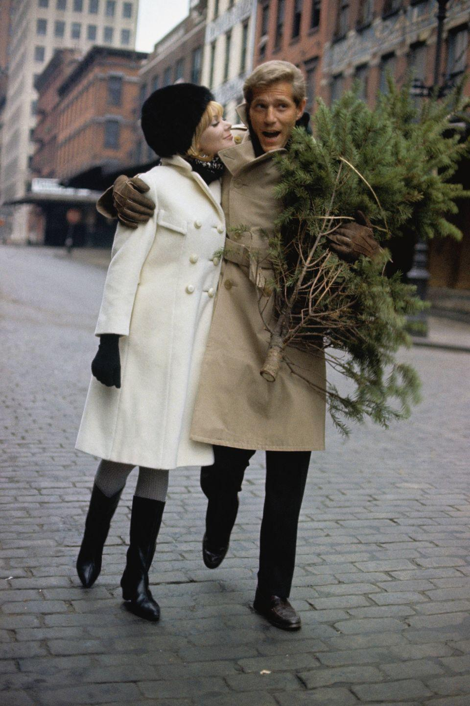 <p>George Segal bundled up in a fashionable beige trench coat, as he strolled through New York City with model Maggy London under one arm and a Christmas tree under the other. </p>