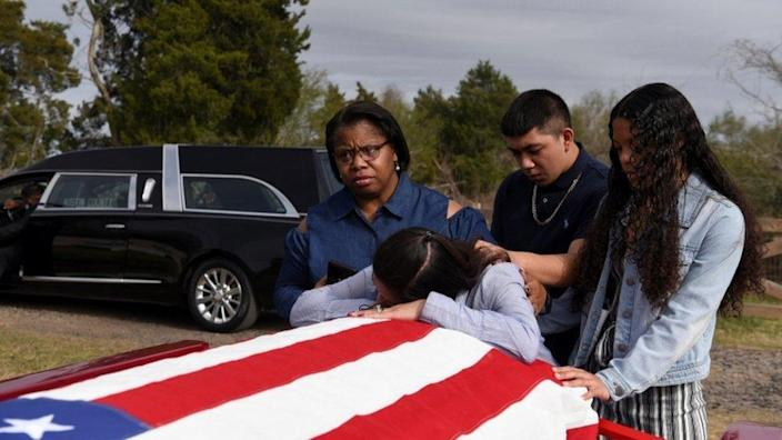 A family says goodbye to their father's flag draped coffin