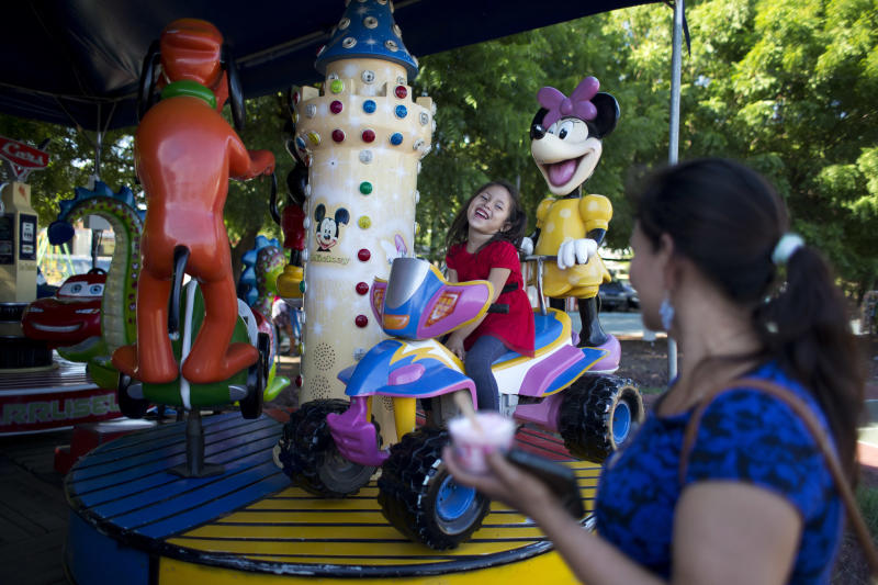 """Five-year-old Alexa laughs with her mother, Araceli Ramos, while riding a merry-go-round at a park in San Miguel, El Salvador, on Aug. 18, 2018. Ramos scraped together $6,000 to pay a smugglerwho could help her escapefrom the man who she said warned her she'd """"never be at peace.""""Onthemonth-long, 1,500-milepilgrimage, she carriedAlexa,a change of clothes, diapers, cookies, juice and water. (AP Photo/Rebecca Blackwell)"""