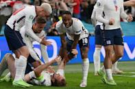 Harry Kane (on the ground) is mobbed by celebrating England players after scoring the extra-time winner against Denmark
