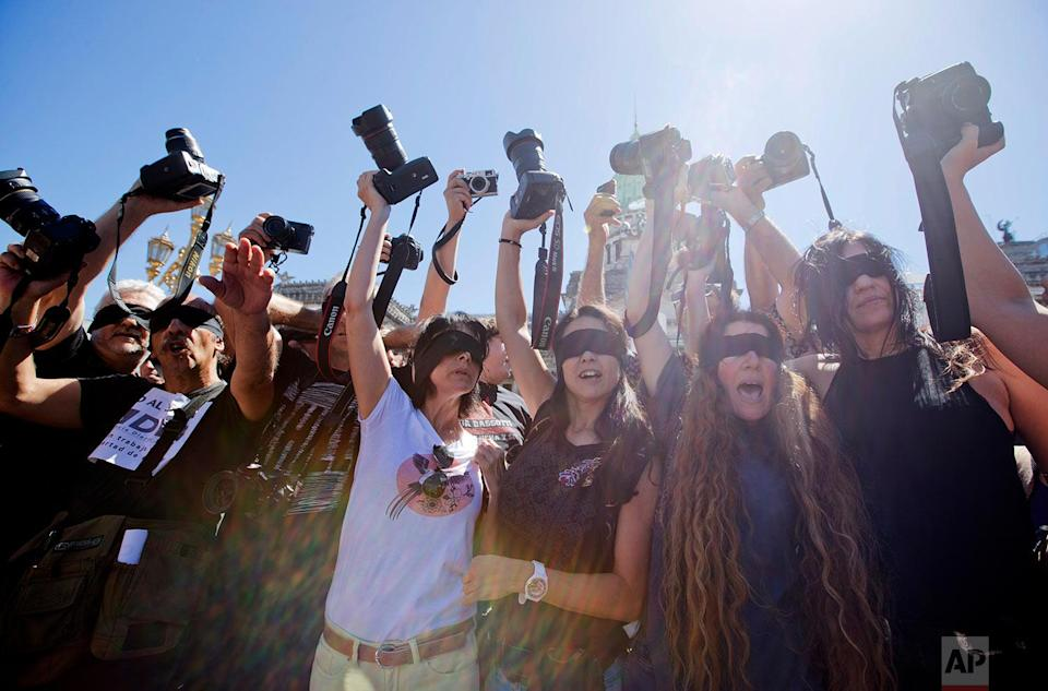 <p>Photojournalists with their eyes blindfolded raise their cameras to protest the closing of the DyN news agency, outside the National Congress in Buenos Aires, Argentina. DyN is the latest in a series of closures of news outlets in Argentina that have left over 2,000 workers unemployed. (AP Photo/Victor R. Caivano) </p>