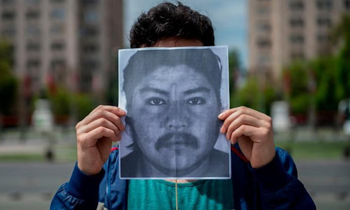 "<span class=""element-image__caption"">A demonstrator holds an image of Camilo Catrillanca in front of La Moneda Palace in Santiago, Chile, on 22 November. </span> <span class=""element-image__credit"">Photograph: Martin Bernetti/AFP/Getty Images</span>"