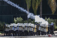 Riot police fire tear gas at Indigenous protesters outside Congress in Brasilia, Brazil, Tuesday, June 22, 2021. Indigenous who are camping in the capital to oppose a proposed bill they say would limit recognition of reservation lands clashed with police blocking them from entering Congress. (AP Photo/Eraldo Peres)