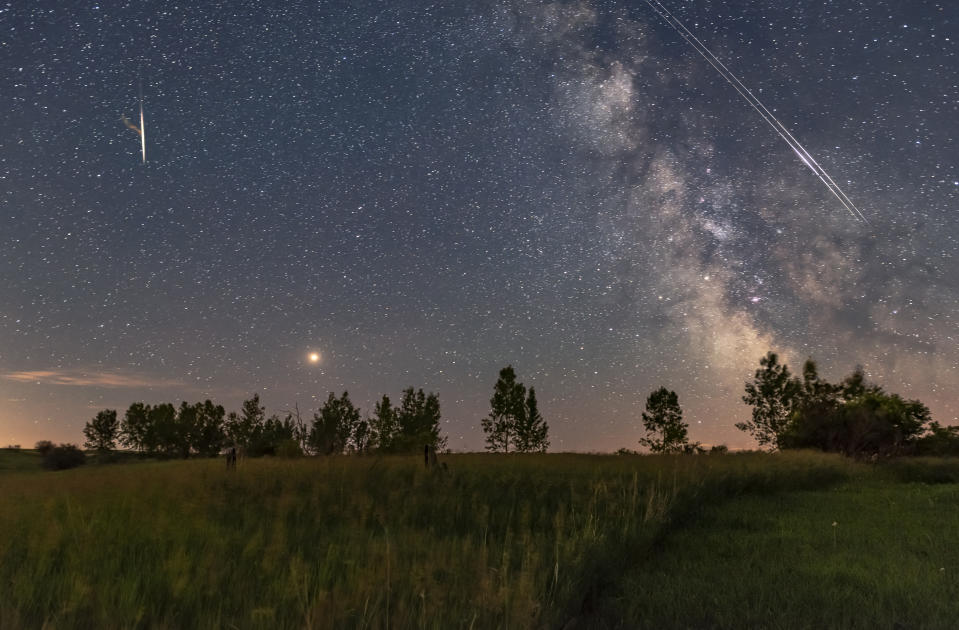 A busy sky with bright red Mars rising east of the Milky Way, while a pair of Iridium satellites flare briefly as they travel in unison up along the Milky Way from south to north.   About 20 minutes later a very bright meteor flared and produced a lasting train of smoke, seen at left and composited in from two later frames - but with it located where it appeared, above Mars. But to be clear - the meteor did not appear at the same time as the Iridiums. Nevertheless, this captures the fact that there were a lot of satellites and meteors this night, on a very clear though short summer night. It was a busy sky!
