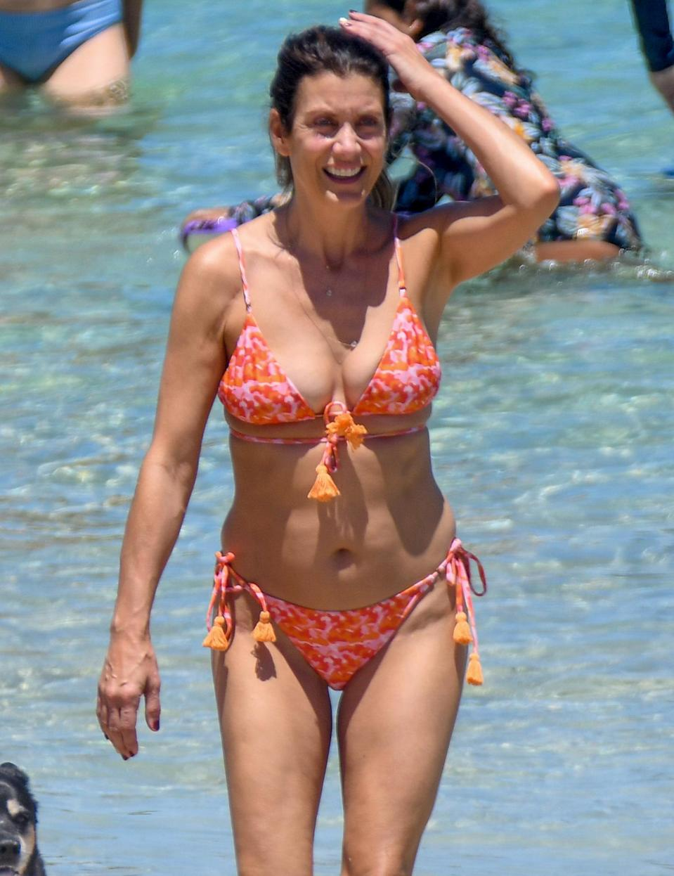 <p>Kate Walsh hits the beach in an orange and pink bikini in Perth, Australia on Tuesday.</p>