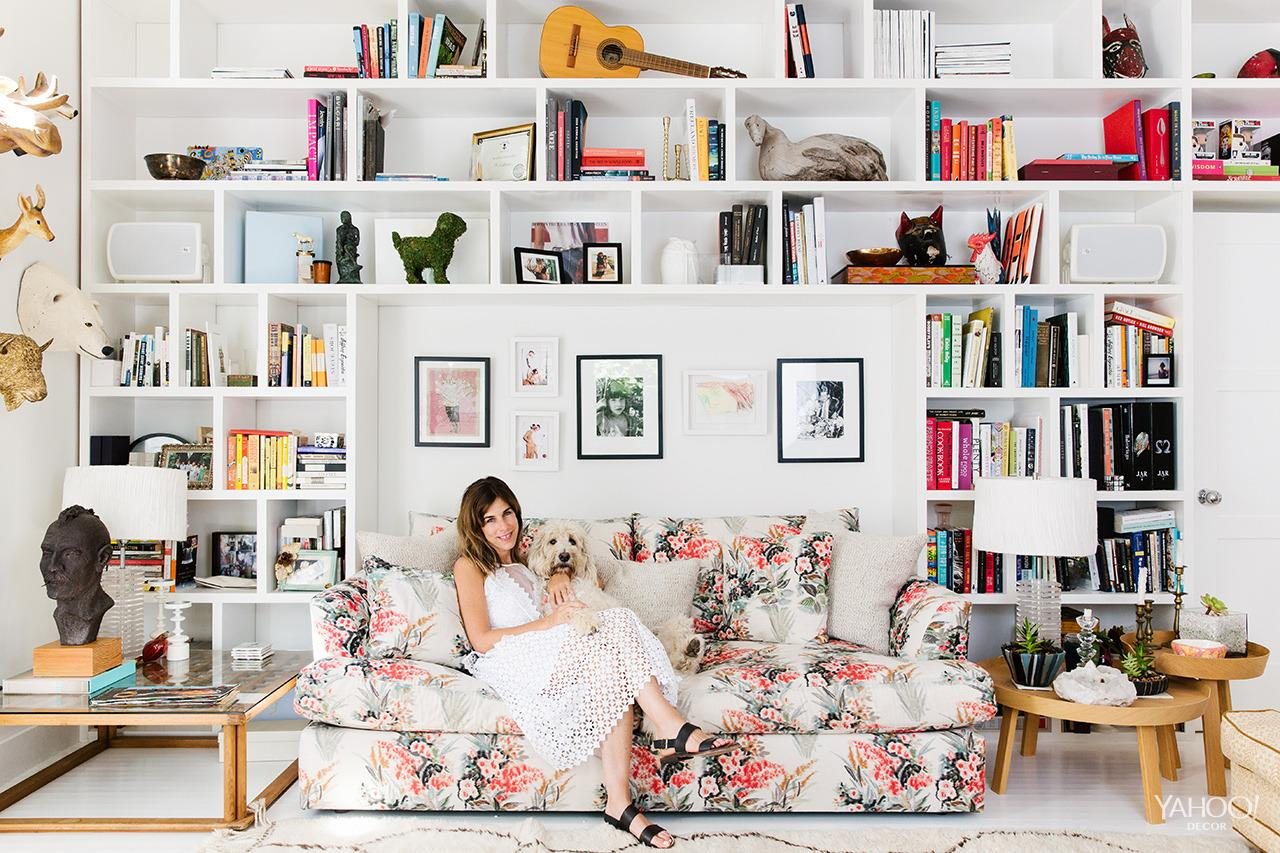"""<p>I'm a big fan of mixing all kinds of patterns together. I love things to be ultrafeminine in a """"Cotton Candy Pink"""" type of way. The fabric on this couch is by Tulu Textiles. My home is a collection of things that I've collected throughout my life, and you can see it on the shelves in this room.</p>"""