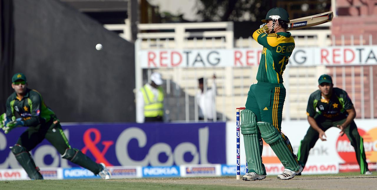 South African batsman Quinton de Kock (C) plays a shot as Pakistani wicket keeper Umar Akmal (L) looks on during the fifth and final day-night international at Sharjah Cricket Stadium in Sharjah on November 11, 2013. South Africa lead the five-match series 3-1. AFP PHOTO/Asif HASSAN