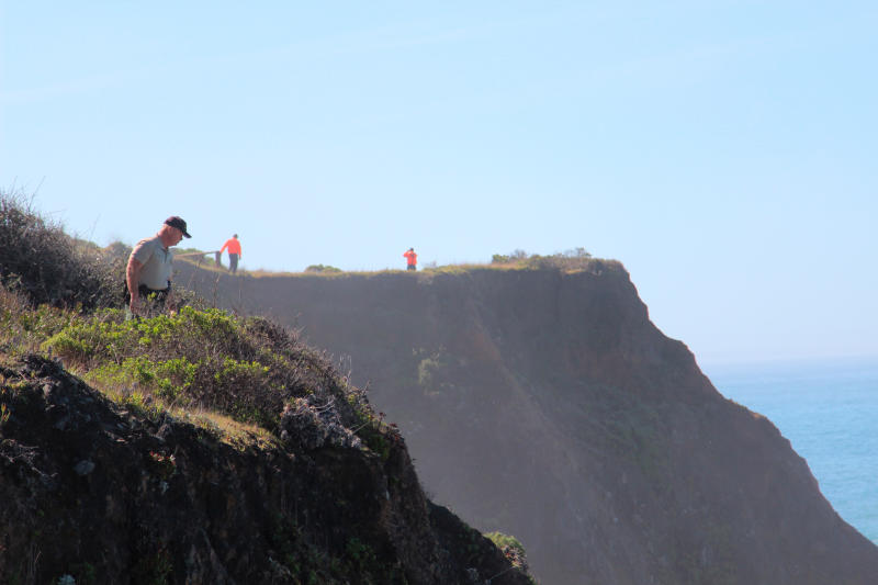 File - In this March 29, 2018, file photo, Deputy Bill Holcomb looks down the cliff near the crash site near Mendocino, Calif., as search and rescue volunteers scour the area behind him looking for three children, still missing after their parent's SUV plunged into the ocean. The Mendocino County Sheriff's office says a team will search the area where an SUV plunged off a Northern California cliff, killing a family of eight last month. The office said Monday, April 9, 2018, in a statement that searchers will take advantage of a low tide and go out around 11 a.m. to try to locate the missing children and any physical evidence. The California Highway Patrol will search the area by helicopter. (Kale Williams/The Oregonian via AP, File)