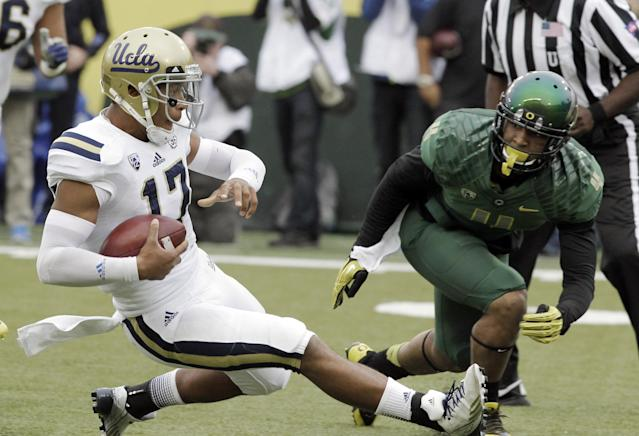 UCLA quarterback Brett Hundley, left, slides in on the run as Oregon defender Erick Dargan moves in during the first half of an NCAA college football game in Eugene, Ore., Saturday, Oct. 26, 2013. (AP Photo/Don Ryan)