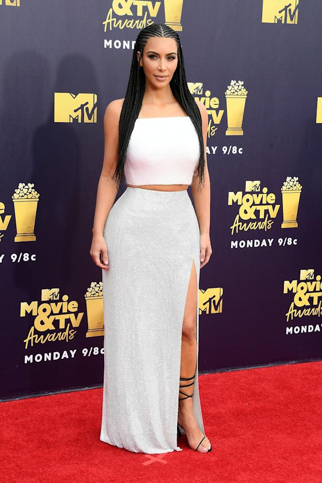 "<p>Wearing a <a href=""https://www.popsugar.com/fashion/Kim-Kardashian-Outfit-MTV-Awards-2018-44951840"" rel=""nofollow noopener"" target=""_blank"" data-ylk=""slk:white crop top and skirt"" class=""link rapid-noclick-resp"">white crop top and skirt</a> by Atelier Versace.</p>"