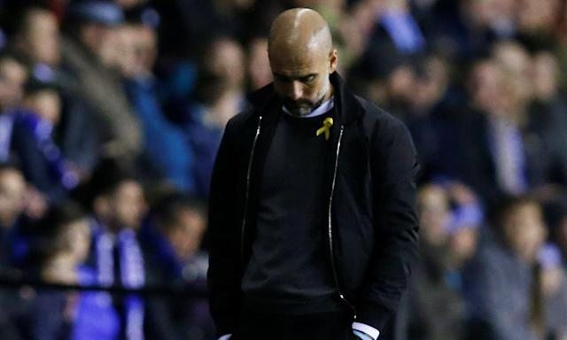 Pep Guardiola, wearing his yellow ribbon in support of jailed Catalan politicians, on the touchline at Wigan.