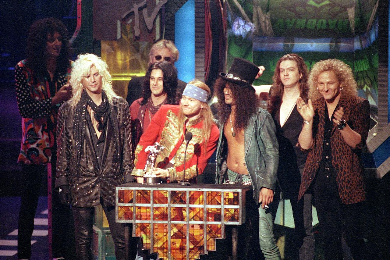 """Guns N'Roses rock group receives the Michael Jackson Video Vanguard Award for """"November Rain"""" at the MTV Video Music Awards ceremony in Los Angeles, Ca., on Sept. 9, 1992.  At the podium are, Axl Rose, left, and Slash.  Joining them on the stage are, from left, Duff McKagan, Gilby Clarke, Dizzy Reed and Matt Sorum.  (AP Photo/Kevork Djansezian)"""