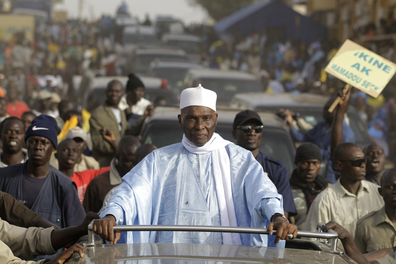 Senegalese President Abdoulaye Wade is surrounded by supporters and security as he travels between campaign stops in downtrodden suburban neighborhoods of Dakar, Senegal Wednesday, Feb. 22, 2012. Thousands of supporters turned out to see Wade as he held rallies in the Pikine and Guediawaye neighborhoods on Wednesday. Daily protests have rocked the capital after the opposition vowed to render the country ungovernable if 85-year-old Wade runs for a third term in Sunday's elections.(AP Photo/Rebecca Blackwell)