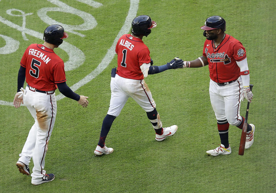 Atlanta Braves' Ozzie Albies (1) is congratulated by Abraham Almonte, right, after hitting a two-run home run off St. Louis Cardinals pitcher Carlos Martinez during the second inning of a baseball game Friday, June 18, 2021, in Atlanta. (AP Photo/Ben Margot)